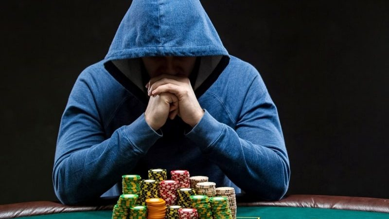 A poker player in front of his chip stack.