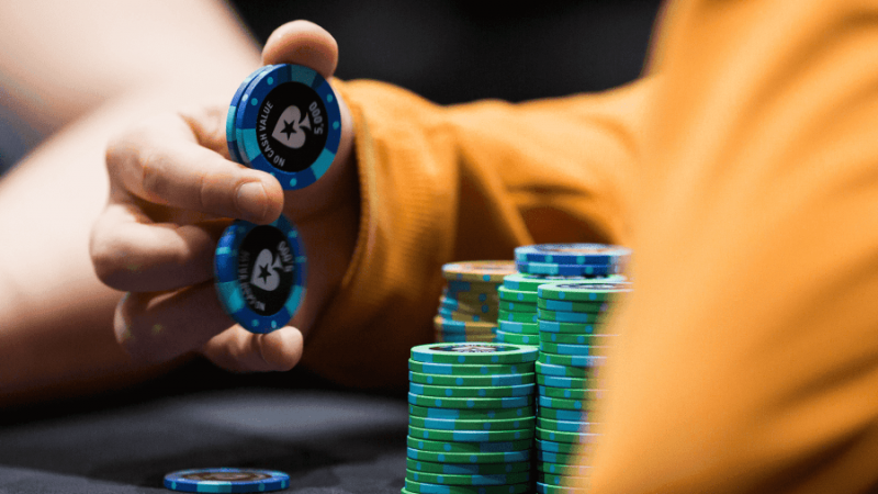 A poker player balancing poker chips in his hands.